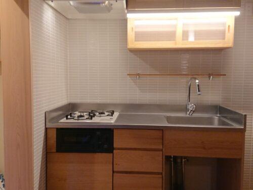 無垢材を使用した製作キッチン。吊戸棚やカップボードに引き出し収納も豊富です。壁面はタイル張り。(キッチン)